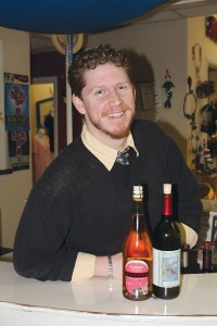 Beau Walker is an employee of Silver Coast Winery Tasting Room and a contributor to Southport Magazine. On the left is a bottle of McKeown's Cranberry Cider, while Silver Coast Winery's own Holiday Red appears on the right. Photo by Bethany Turner