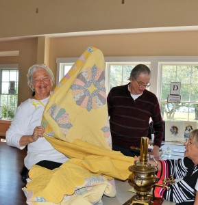 Judy Bowers displays her antique quilt, while Robert Brown (center) and Carol Mahoney (right) examine the piece. Brown and Mahoney are both appraisers from Northrop Antiques Mall in Southport. Courtesy photo
