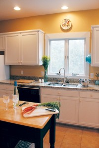 The kitchen features an island and brand-new granite countertops. Photo by Bethany Turner