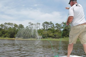 Captain Alan Beasley tossing the cast net out to catch some live bait last month. Photo by Kris Beasley