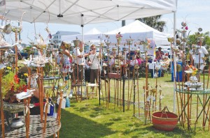 Guests of a past Oak Island Art Guild Arts and Crafts Festival peruse metal works crafted for lawn and garden use. Courtesy photo