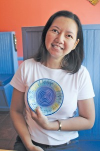 Thitima Sanitniam, better known as Gai, opened Thai by the Sea on Oak Island 11 years ago. The colorful bowl she holds is the only one left of a set that was inspiration for the upbeat color palette used in the restaurant. Photo by Bethany Turner