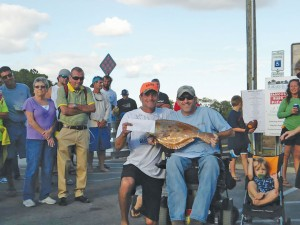 Fisherman Mike Hill (left) accepts the first place prize, $1,000 and  a 24-inch copper trophy, during the 2013 Bay Creek Classic. Hill is pictured with Brandon Matthews (right), a local Southport fishing legend whose medical bills are supported by proceeds of the Bay Creek Classic. Courtesy photo