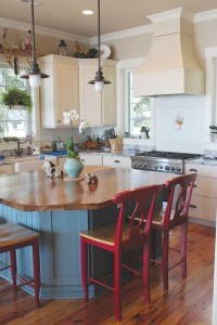 The kitchen remains coastal with its light, airy feel, while accents such as subway tiles, a farmhouse sink, and red bar chairs offer country-chic style. Photo by Bethany Turner