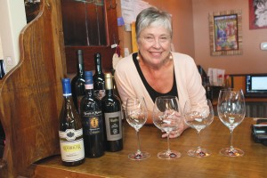 Candace Hobbs, owner of The Grape & Ale, displays various crystal wine glasses crafted by Riedel, which enhance the flavors of each varietal as well as the experience of enjoying wine. Photo by Kris Beasley